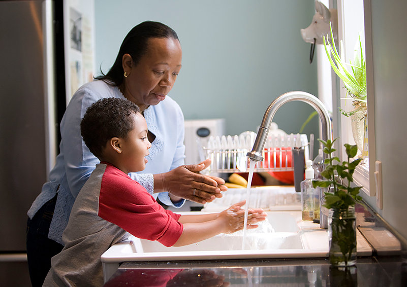 Mother & son wash hands at kitchen sink, plants in windowsill