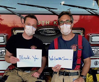 "Two firemen wearing face masks sitting on the front of a red firetruck, holding signs that say ""Thank You"" and ""We Got This Seattle"""