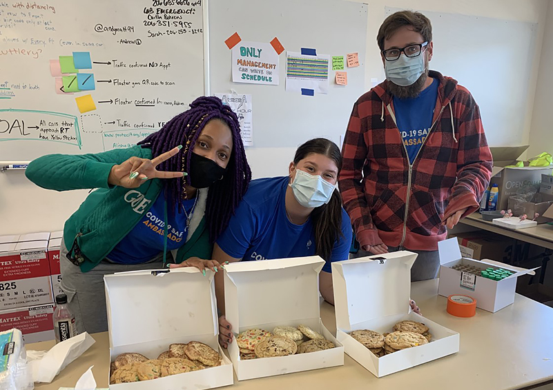Three healthcare workers wearing masks with boxes of donated cookies