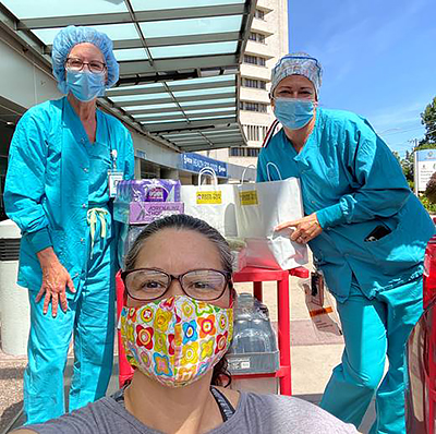 Two healthcare workers in aqua scrubs and one woman in glasses and a colorful mask take a selfie in front of bags of donated food on a red rolling cart