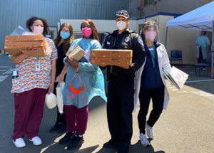 Five healthcare workers with donated food boxes