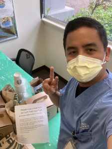 A healthcare worker with peace sign and donated coffee