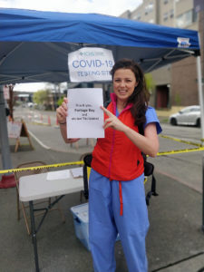 A healthcare worker with the thank you sign