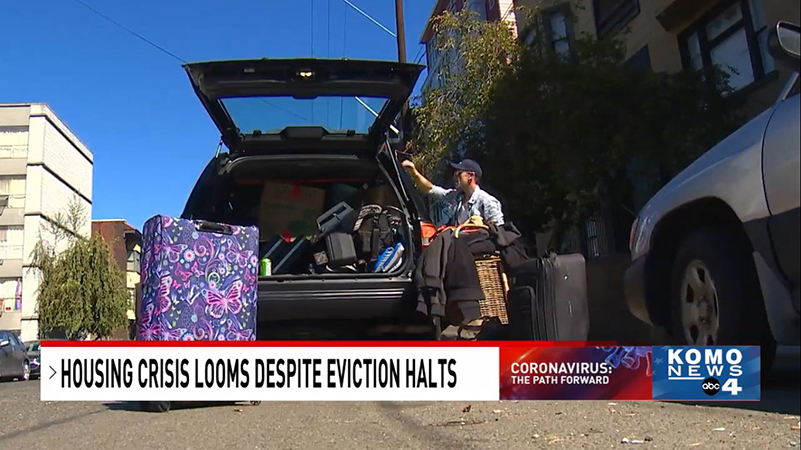 Screenshot from KOMO News story of a man in a cap and sunglasses loading belongings into the back of a station wagon; caption reads, HOUSING CRISIS LOOMS DESPITE EVICTION HALTS