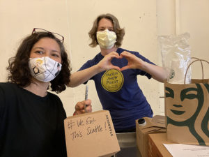 Two healthcare workers with love sign