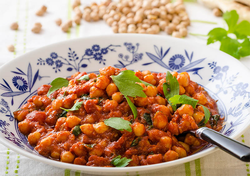 blue and white bowl with black spoon, filled with orange garbanzo beans, chana masala