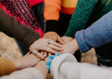 multi-racial grouping of hands, overlapping in center of a circle, arms clothed in colorful sweaters, showing cooperation