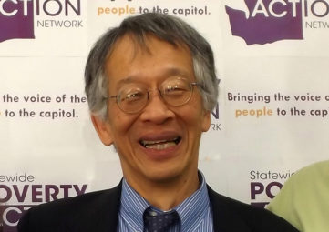 Headshot of an Asian man with greying hair and wire-rimmed glasses, grinning into the camera