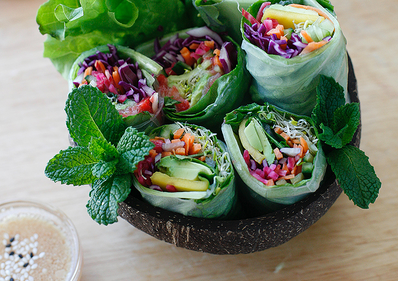 fresh spring rolls filled with colorful veggies in a black bowl with a sprig of mint