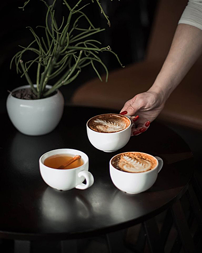 an arm reaching out to a small black table with three lattes in white mugs