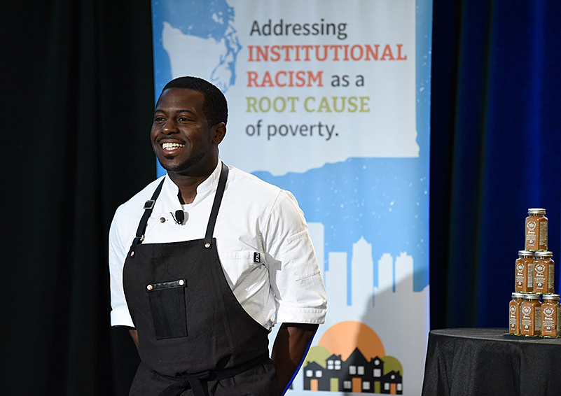 Black chef in a white shirt and black apron in front of a banner reading Addressing INSTITUTIONAL RACISM as a ROOT CAUSE of poverty.