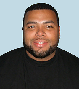 Headshot of a Black man with a beard wearing a black T-shirt with a light blue background