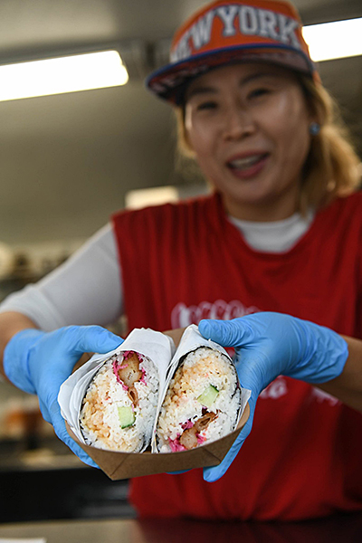 An Asian woman in a red shirt and orange NEW YORK hat holds out a to-go plate of sushi burritos