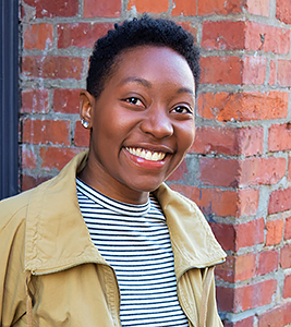 Headshot of smiling Black woman, with short hair, wearing a black & white striped shirt and tan jacket in front of a brick wall