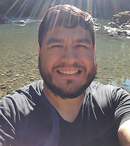 selfie headshot of a latinx person in a black T-shirt in front of a streambed with sunbeams shining on their head