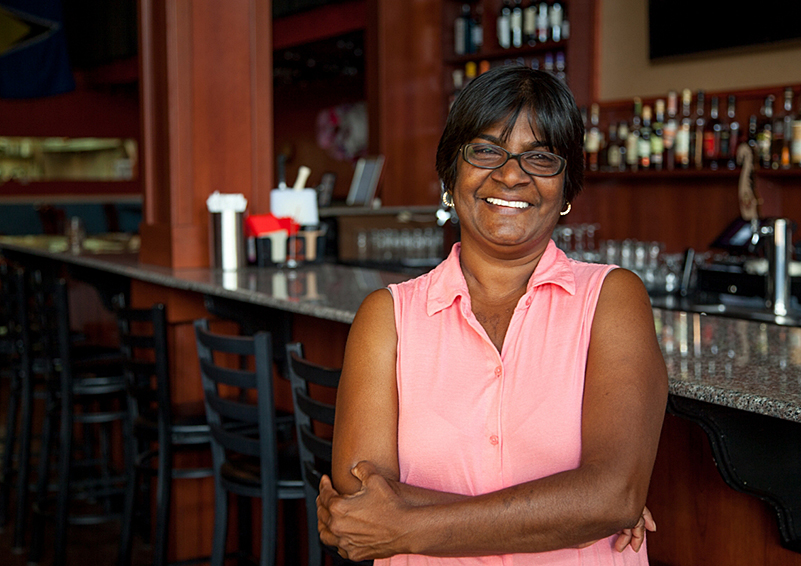 A Black woman restaurant owner smiles in front of a bar