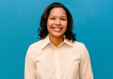 Portrait headshot of woman in a white button-down shirt with blue background.