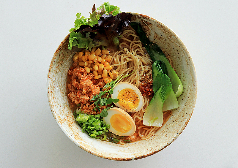 big white ceramic bowl filled with ramen noodles, vegetables, and halved hard-boiled eggs, with a sprig of cilantro