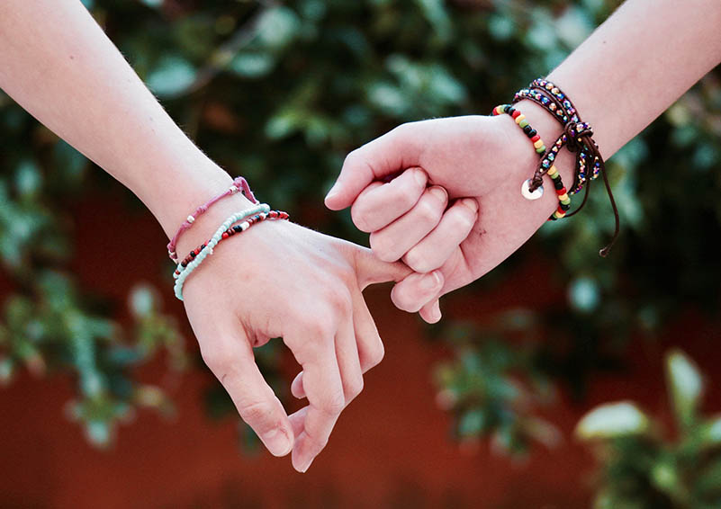 """Two preteen hands with beaded bracelets on """"holding pinkies"""""""