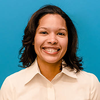 Headshot of a Black woman in a white button-down shirt with blue background.