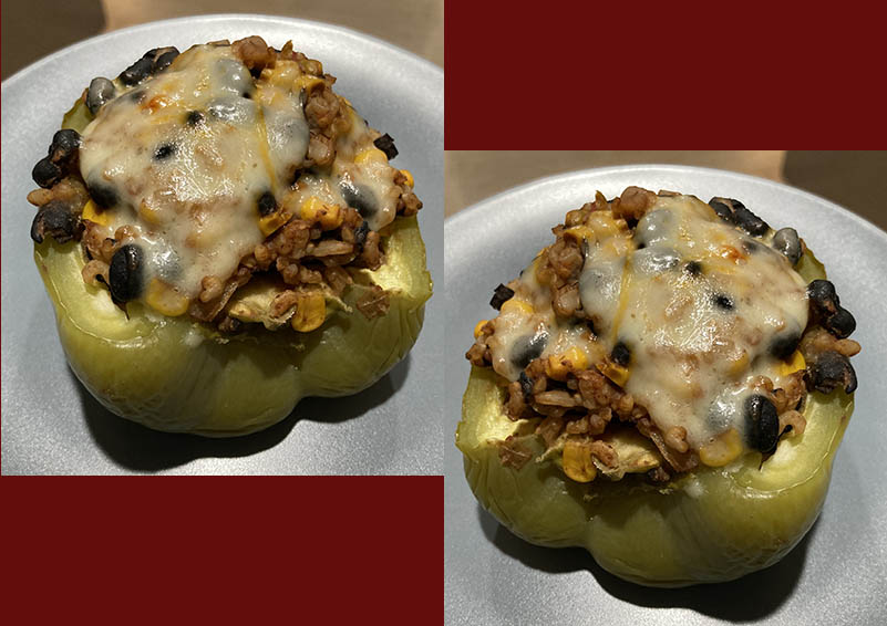 Two stuffed green bell peppers topped with melted cheese on a brick red background