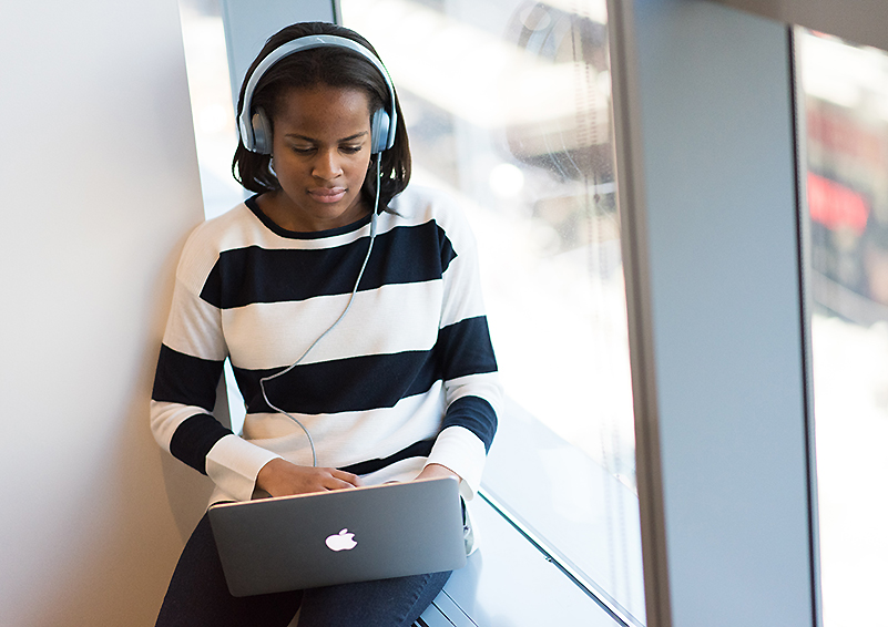 Black teen girl in black and white striped top sits in an office window working on a laptop with headphones on.
