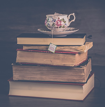 Stack of vintage hard-bound books with a flowery china teacup on top