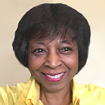 Headshot of a smiling Black woman in a yellow collared shirt