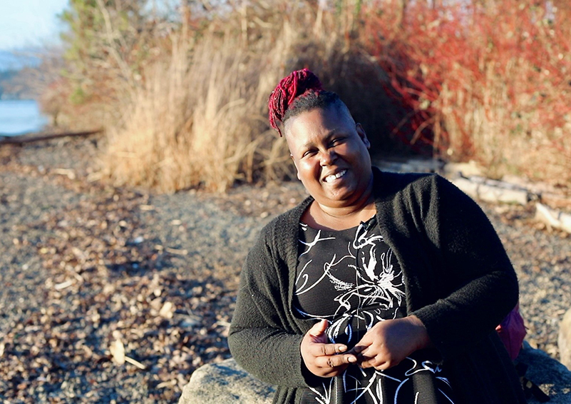 Video still of a Black woman sitting on a rock on a shoreline, smiling broadly