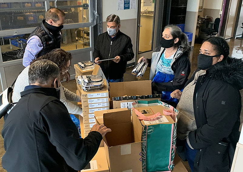 Three women and three men wearing masks, sorting and organizing boxes of donated headsets and other tech items
