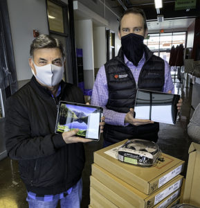 Two men wearing masks holding donated tablets stand behind a table of boxes of headsets.