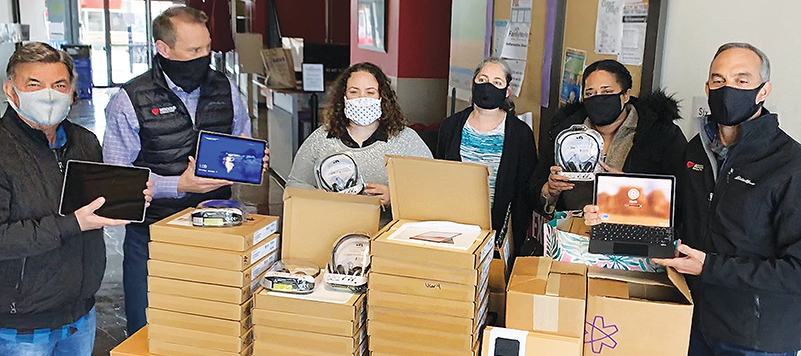 Three men and three women wearing masks pose behind a table of donated tech tools (headsets, tablets, etc.)
