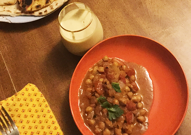 Table setting with a bright orange plate with Butter Chickpeas on it, a glass of kefir, the corner of a plate of naan, and a bright yellow napkin with a fork on it