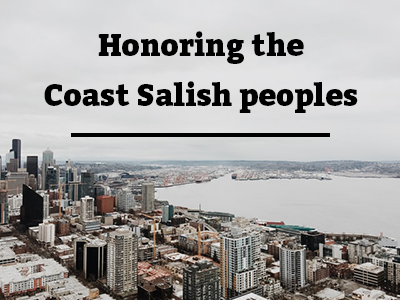 Photo of the downtown Seattle waterfront with a grey sky and black text reading Honoring the Coast Salish People