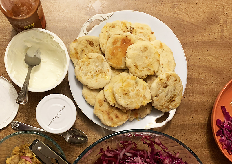 Pupusas on a white plate next to a plate of red cabbage slaw and other condiments