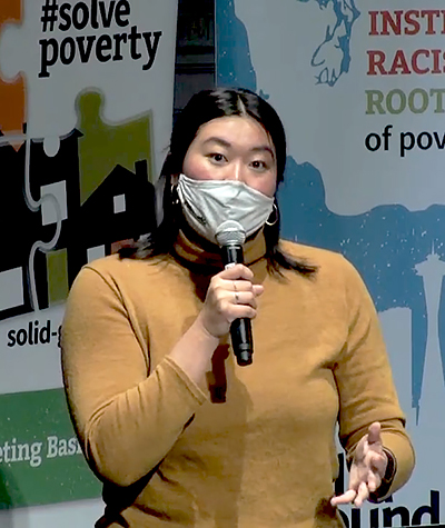 Asian woman in a tan turtleneck sweater and wearing a mask, speaks into a microphone