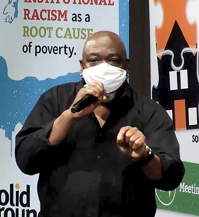 Black man in a black shirt and wearing a mask, speaks into a microphone