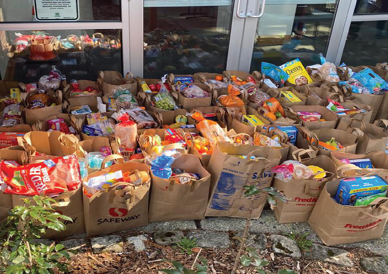 50 or so full paper grocery bags stacked outside of a food pantry