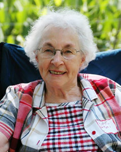 Photo of an elderly white woman with white hair and glasses, smiling