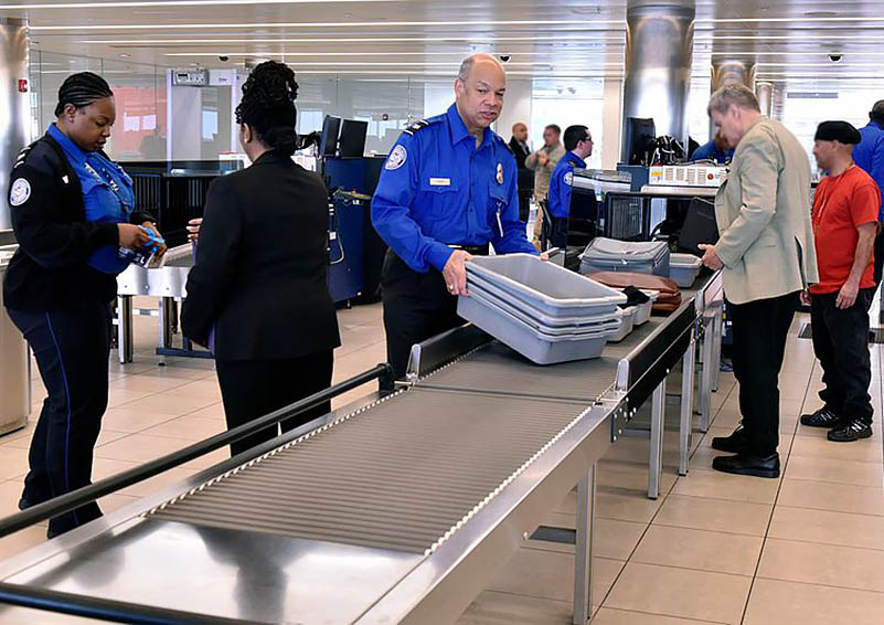 Two TSA in royal blue shirts work at the baggage security area