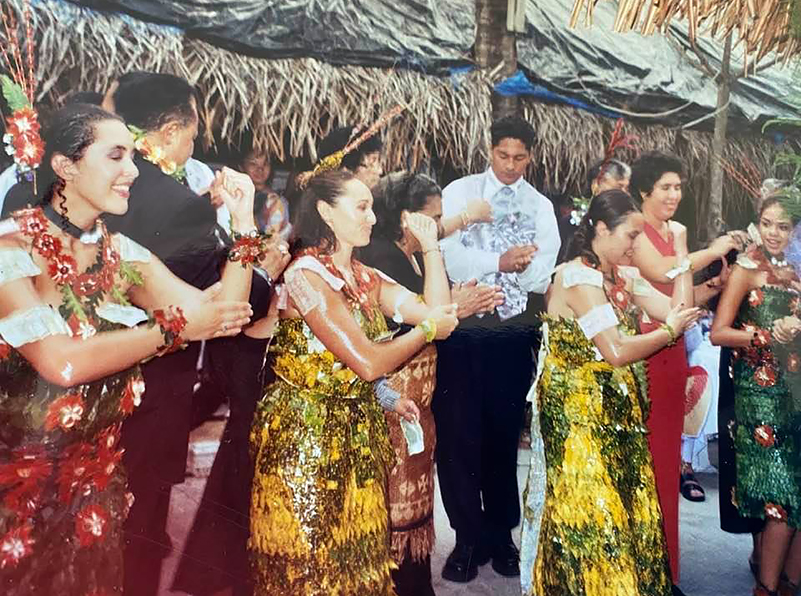 Group of Tongan women in colorful dresses dancing at a wedding