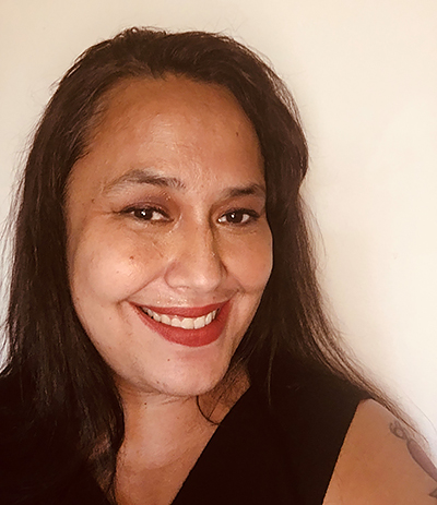 Headshot of a Tongan American woman smiling with dark brown hair, wearing a black tank top