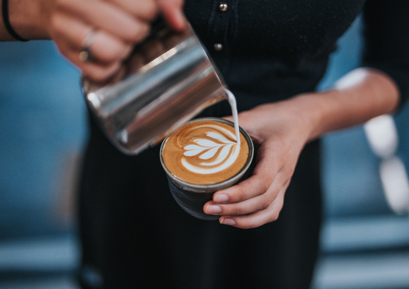 A barista pouring a latte