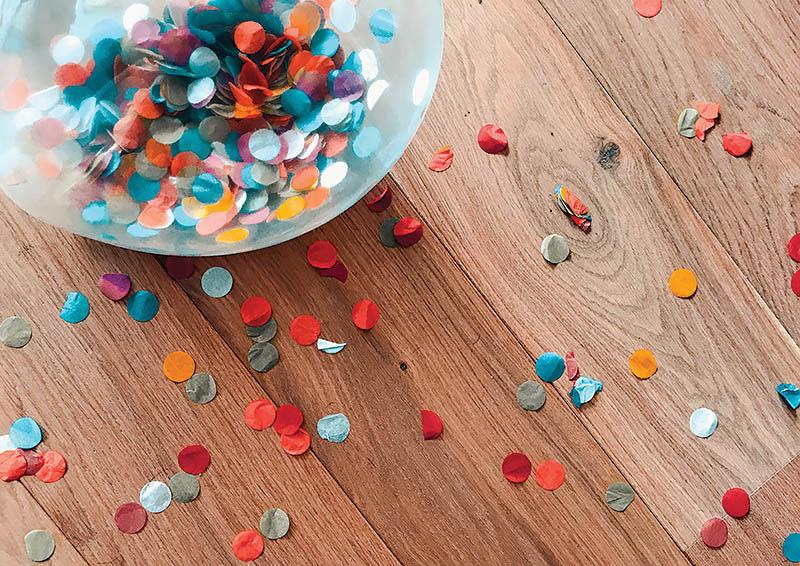 Colorful bowl of confetti on a wooden table strewn with confetti