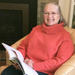 White-haired woman with glasses wearing a pink turtleneck top smiles from a reading chair with a large book open in her lap.