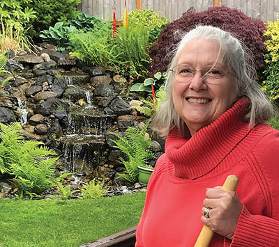 White woman with grey hair and wire-rimmed glasses, wearing a red turtleneck sweater, poses holding a rake in front of her lush, green, landscaped garden and waterfall