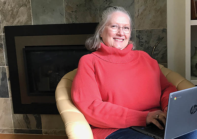 White woman with grey hair and wire-rimmed glasses, wearing a red turtleneck sweater, sitting in a beige chair with a laptop on her lap