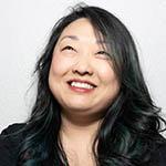 Headshot of a Korean woman with long black hair wearing a black top, smiling and gazing upward
