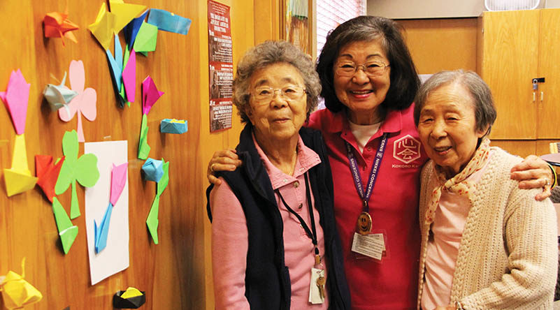 Three senior Japanese woman stand with their arms around each other next to a wall of colorful origami creations