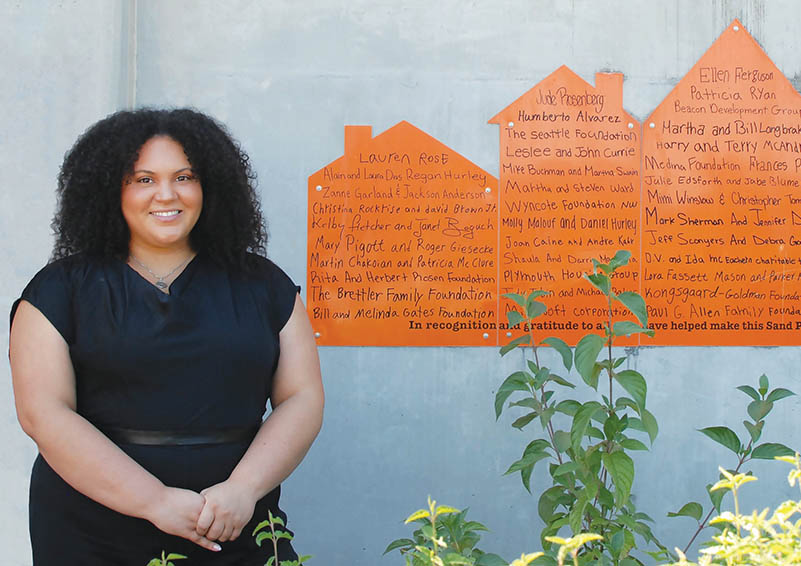 Black woman with curly shoulder-length hair wearing all black stands in front of a concrete wall with a commemorative orange plaque in the shape of houses, listing donor names.